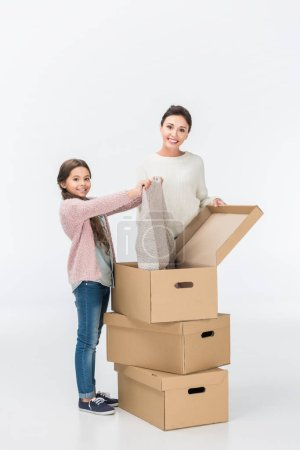 Photo for Happy mother and daughter with cardboard boxes moving to new house isolated on white - Royalty Free Image