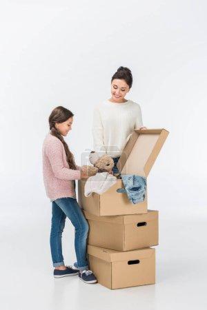 Photo pour Souriant de la mère et la fille avec des boîtes en carton, passer à la nouvelle maison isolé sur blanc - image libre de droit