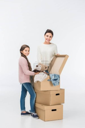 Photo for Mother and daughter with carton boxes moving to new house isolated on white - Royalty Free Image