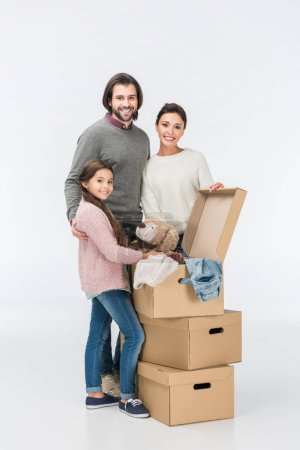 Photo for Happy family with cardboard boxes moving to new house isolated on white - Royalty Free Image