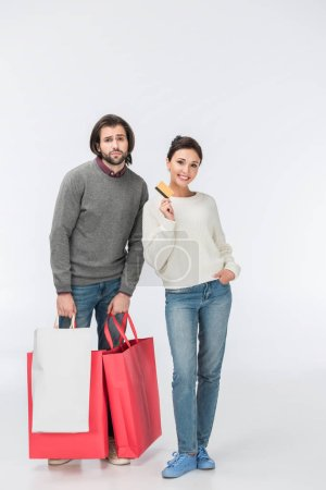 Photo for Thoughtful man with shopping bags and smiling woman showing credit card isolated on white - Royalty Free Image