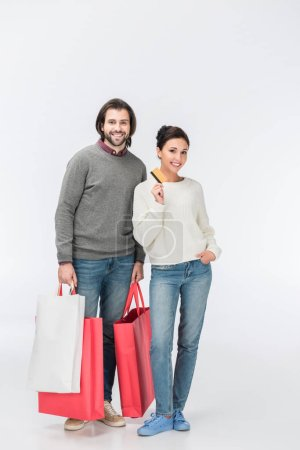Photo for Man with shopping bags and woman showing credit card isolated on white - Royalty Free Image
