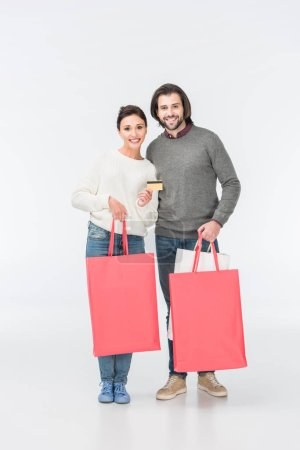 smiling couple with shopping bags and woman showing credit card isolated on white