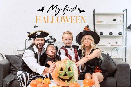 """Foto de Retrato de familia en diversos disfraces de halloween en mesa con calabazas en casa con """"mi primer halloween"""" Letras - Imagen libre de derechos"""