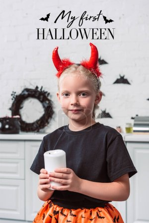 """portrait of little kid with red devil horns holding candle in hands at home, with """"my first halloween"""" lettering"""