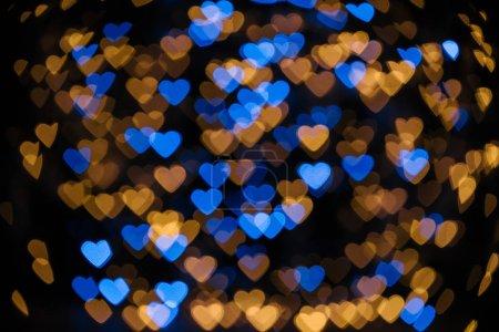 full frame of golden and blue defocused hearts bokeh lights on black background