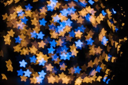 full frame of blue and golden stars bokeh lights on black backdrop