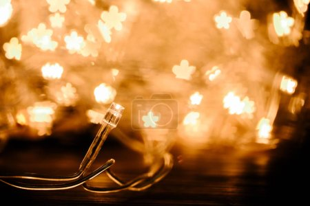 close up view of festive garland and stars bokeh lights backdrop