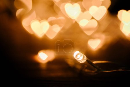 Photo for Close up view of festive garland and hearts bokeh lights backdrop - Royalty Free Image