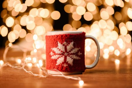 close up view of cup of hot drink and garland on wooden tabletop with bokeh lights background