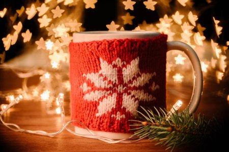 close up view of cup of hot drink, garland and pine tree branch on wooden tabletop with stars bokeh lights background