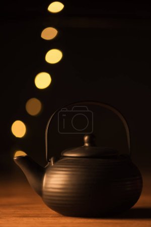 close up view of clay teapot and golden bokeh lights as steam on black background