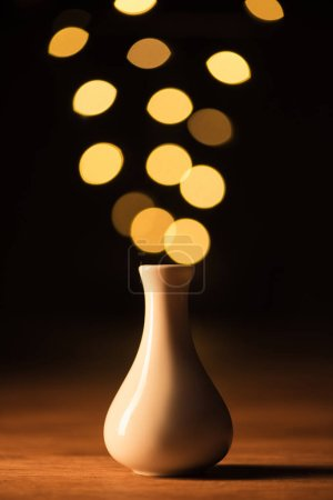 close up view of white vase and yellow bokeh lights on black background