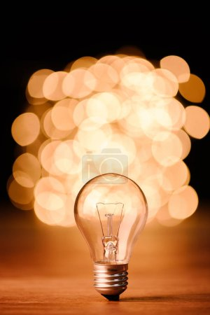 close up view of light bulb and bokeh lights on background