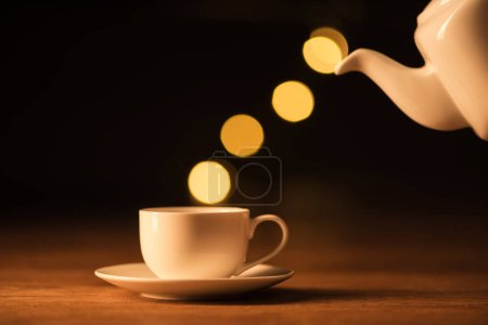 close up view of white teapot, cup of coffee and bokeh lights on black backdrop