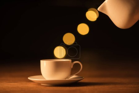 close up view of white jug, cup of coffee and bokeh lights on black backdrop