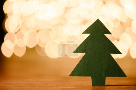 close up view of green paper christmas tree on wooden tabletop and bokeh lights background with copy space