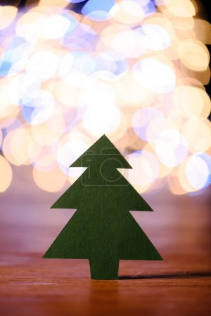 close up view of green paper christmas tree on wooden tabletop and bokeh lights background