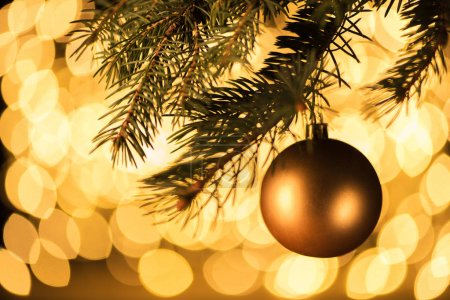 close up view of golden christmas ball hanging on pine tree with bokeh lights background
