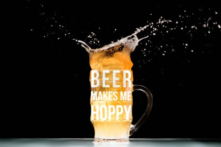 "mug of light  beer with foam and splashes at table on black background with ""beer makes me hoppy"" inspiration"