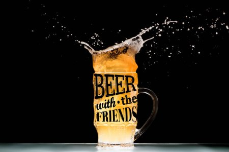 "mug of light  beer with foam and splashes at table on black background with ""beer with the friends"" inspiration"