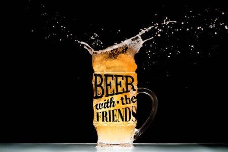 """tasse de bière légère avec mousse et éclaboussures à table sur fond noir avec inspiration """"bière avec les amis"""""""