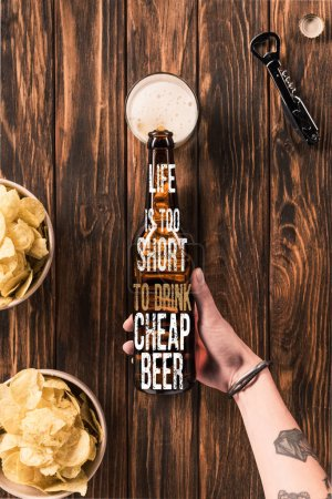 """Photo for Cropped image of woman pouring beer into glass at wooden table with crispy chips, with """"life is too short to drink cheap beer"""" inspiration - Royalty Free Image"""