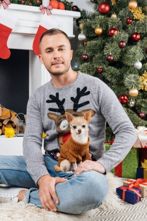 man in sweater with deer with little chihuahua dog in decorated room for christmas