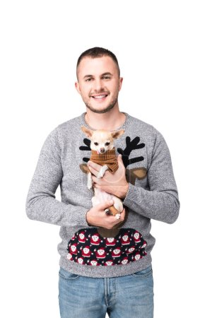 portrait of smiling man in festive winter sweater holding cute little chihuahua dog isolated on white