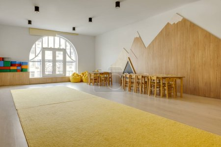 playing room interior with wooden chairs and tables, yellow carpet, bean bag chairs and bright blocks in kindergarten