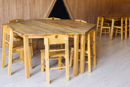 wooden tables and small chairs in kindergarten room