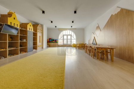 cozy kindergarten classroom interior with yellow carpet, tables and tv