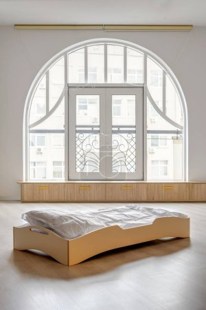 single wooden bed with white bedding in light kindergarten room