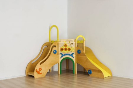 beautiful bright wooden slides in playing room at kindergarten