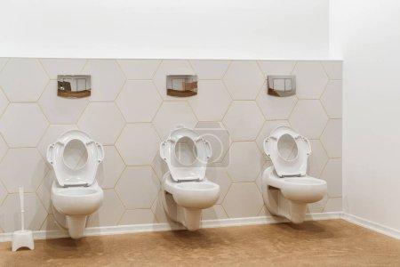 clean white toilet bowls in toilet in modern kindergarten