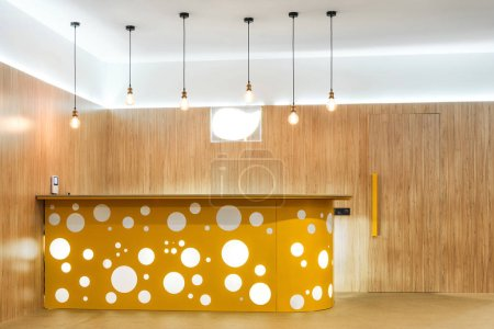 lamps and yellow reception desk in modern kindergarten interior
