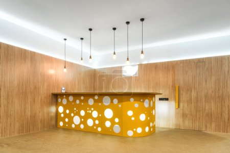 illuminated lamps and yellow reception desk in modern kindergarten