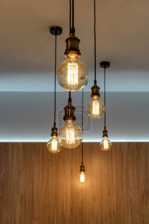 Photo for Close-up view of illuminated light bulbs hanging in empty room - Royalty Free Image