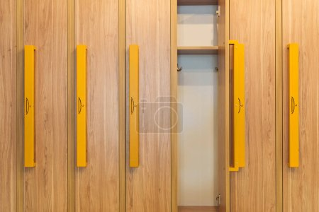 wooden lockers with yellow handles in kindergarten cloakroom