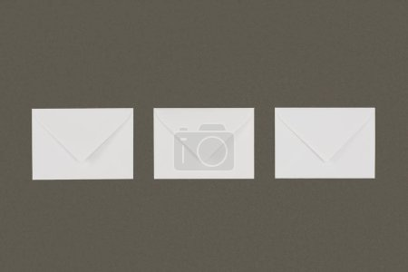Photo for Top view of three closed white envelopes arranged isolated on grey background - Royalty Free Image