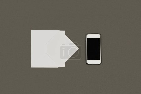 top view of white envelope, blank card and smartphone with blank screen isolated on grey