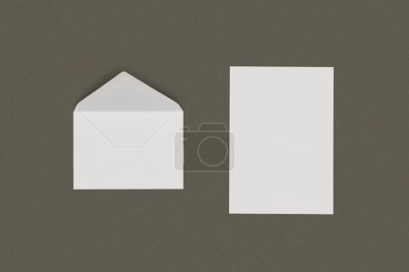 top view of open white envelope and blank card isolated on grey background