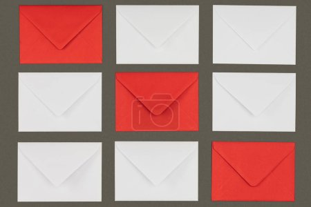 close-up view of closed red and white envelopes isolated on grey background