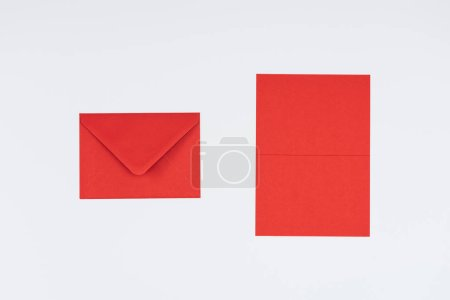 close-up view of closed red envelope and card isolated on white