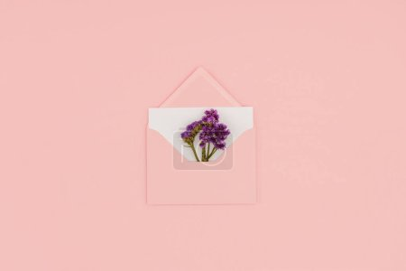 top view of open pink envelope with white card and small purple flowers isolated on pink