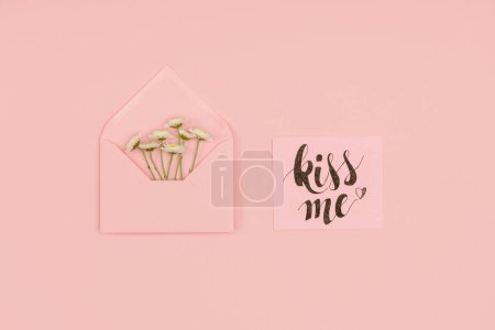 top view of open pink envelope with small white flowers and card with kiss me inscription isolated on pink