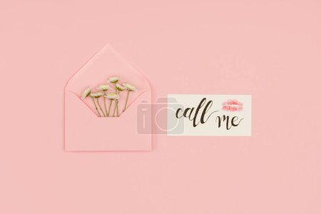 top view of open pink envelope with small white flowers, card with call me inscription and kiss mark isolated on pink
