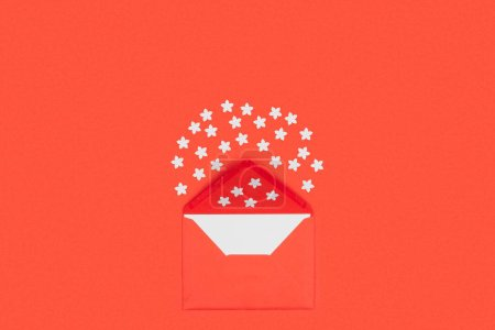 top view of open red envelope with blank card and small white stars isolated on red