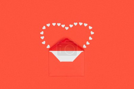 top view of red envelope with white card and small hearts isolated on red