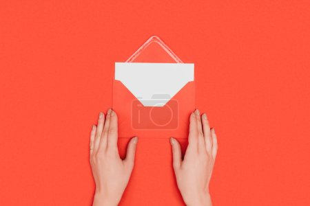 cropped shot of person opening envelope with card isolated on red